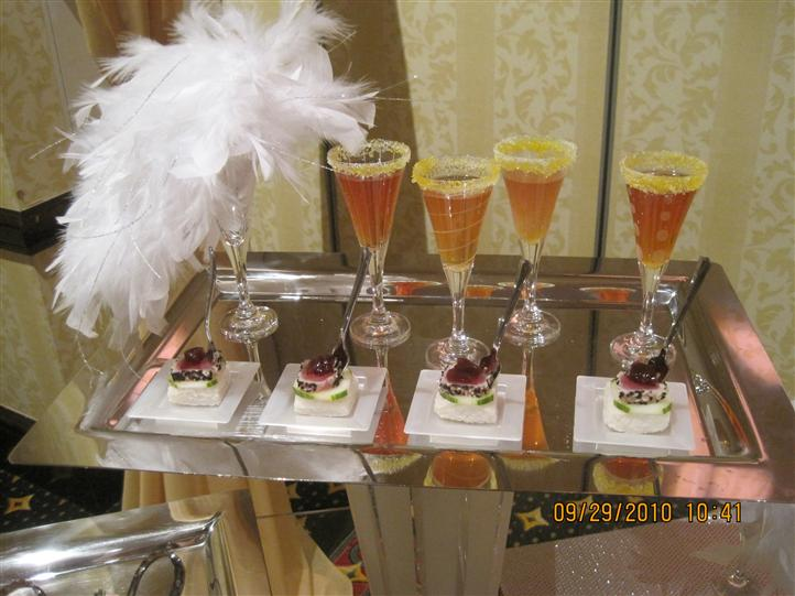Four glasses of cocktails and four small square white plates with bites