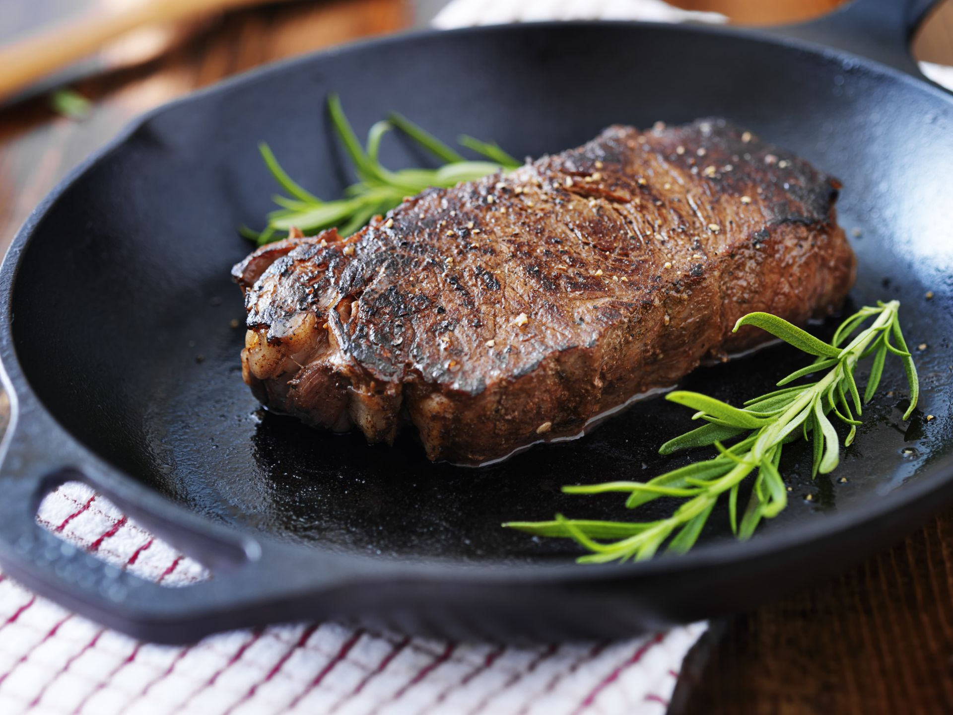 steak on a pan with rosemary