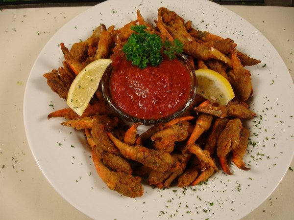 fried crab claws with dipping sauce and lemon wedges