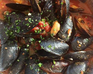 mussels in a pot with tomatoes and parsley as a garnish