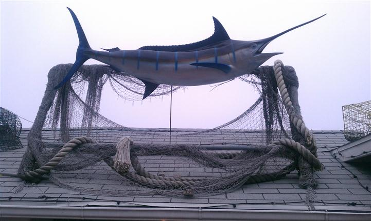 closeup of the swordfish statue on the roof of mike's seafood