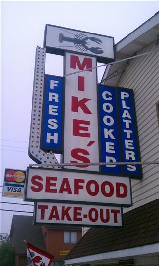 a closeup of the mike's seafood sign that also says takeout, fresh, cooked and platters on it