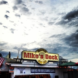 a view of mike's dock seafood raw bar sign with a cloudy sky