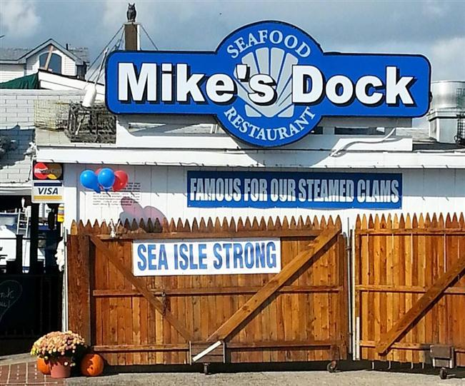 "the outside view of mike's dock seafood resturant with a ""Famous for our steamed clams"" and ""Sea isle strong"" sign"
