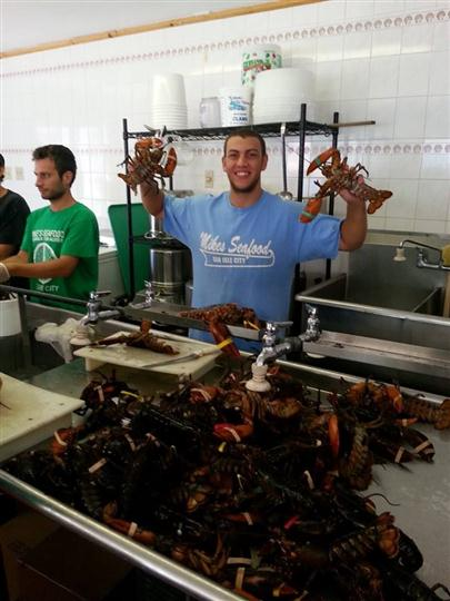workers holding up the cooked lobsters in the kitchen