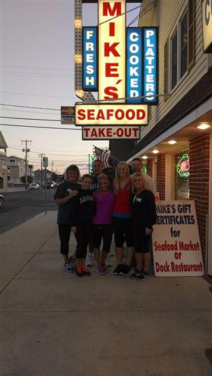 a group of 9 people posing under the mike's seafood sign