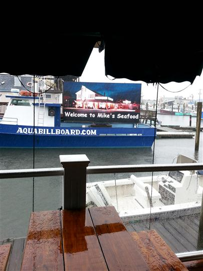 "a billboard on a boat that says ""welcome to mike's seafood"" with a photo of the storefront"