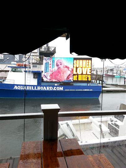 "a billboard on a boat that says ""Summer love at mike's"""