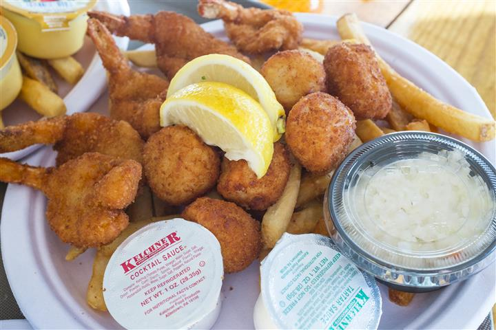 fried clams and hushpuppies with a side of fries, tartar sauce and lemon wedges