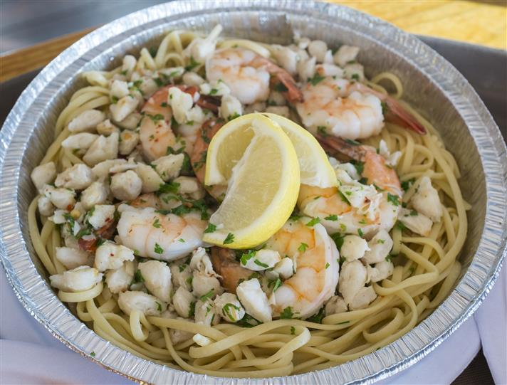shrimp linguini with scallops and lemon wedges