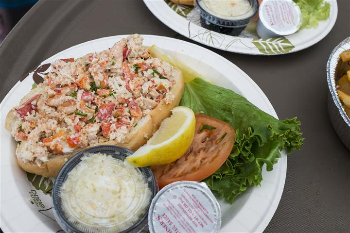 a lobster roll with a side of cole slaw, a lemon wedge, lettuce and a tomato slice