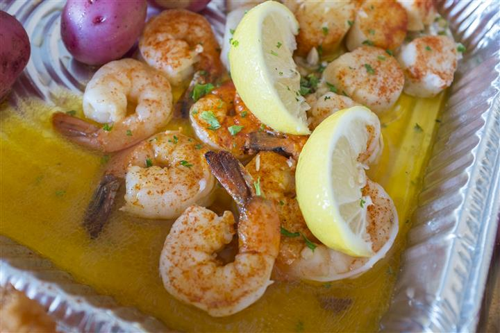 shrimp in an oil sauce with lemon wedges