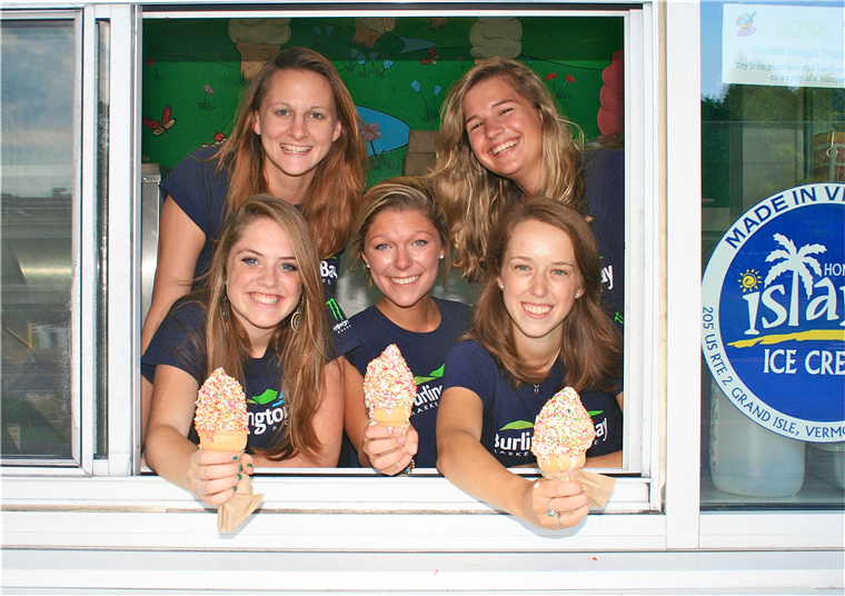 employees smiling with three holding ice cream cones