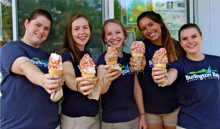 five employees smiling and holding soft serve ice cream cones