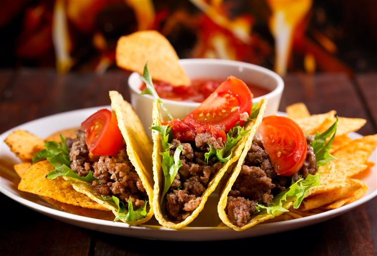 three tacos with meat, lettuce and tomato with dipping sauce on the side