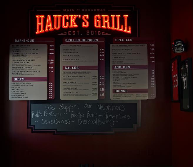 Hauck's Grill sign on wall with menus and chalkboard