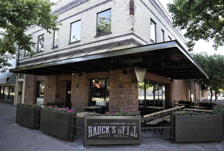 Haucks grill storefront showing outdoor tables and chairs