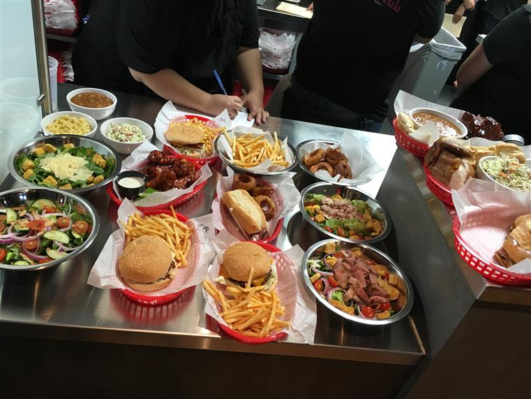Spread of burgers, fries, wings on table