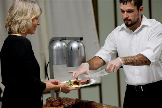 catering associate serving a plate of food