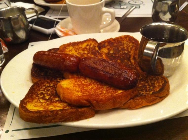 French toast with sausage on white plate