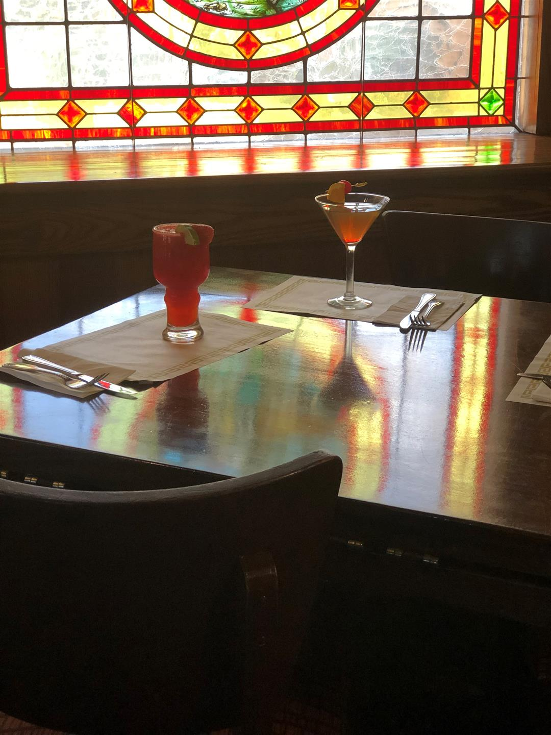 Two cocktails on wooden table in front of stained glass window