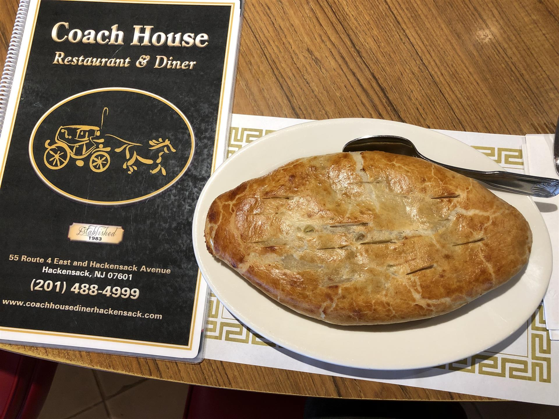 Chicken Pot pie with a fork in it next to Coach House Diner menu