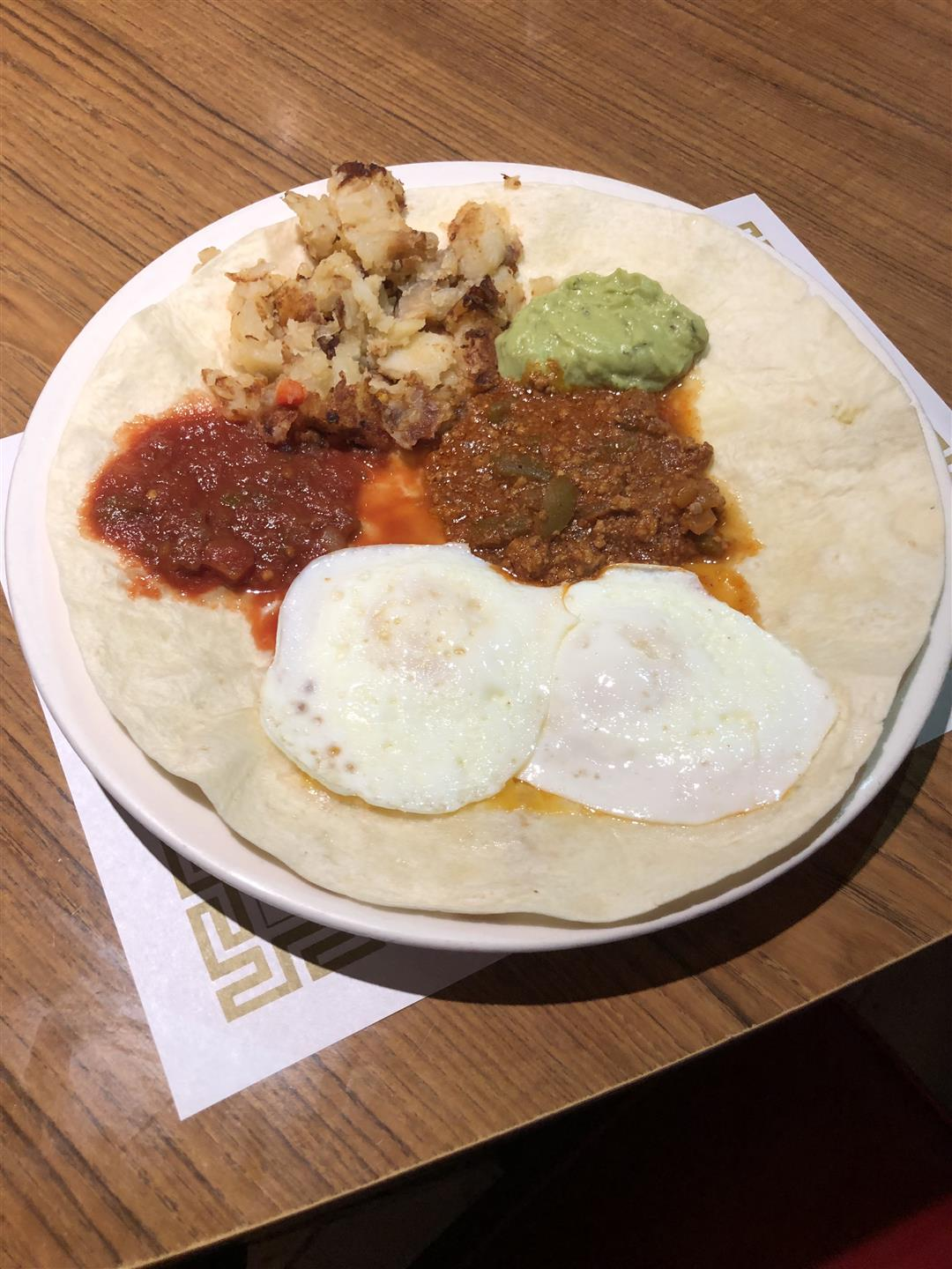 Two fried eggs, cheddar cheese, salsa & guacamole on a tortilla.