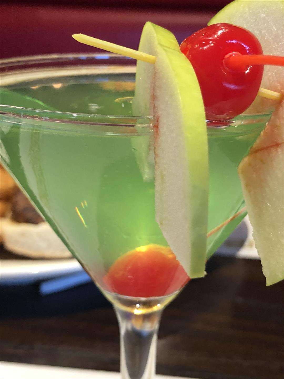 Green cocktail in a martini glass with a lemon wedge and a cherry