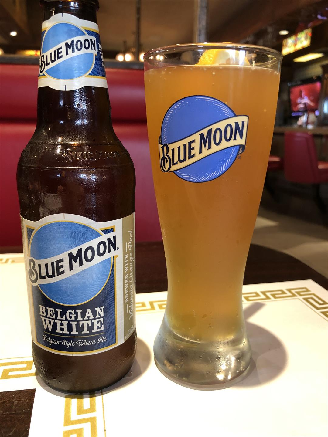 Blue Moon Beer in a bottle and  a cup next to each other