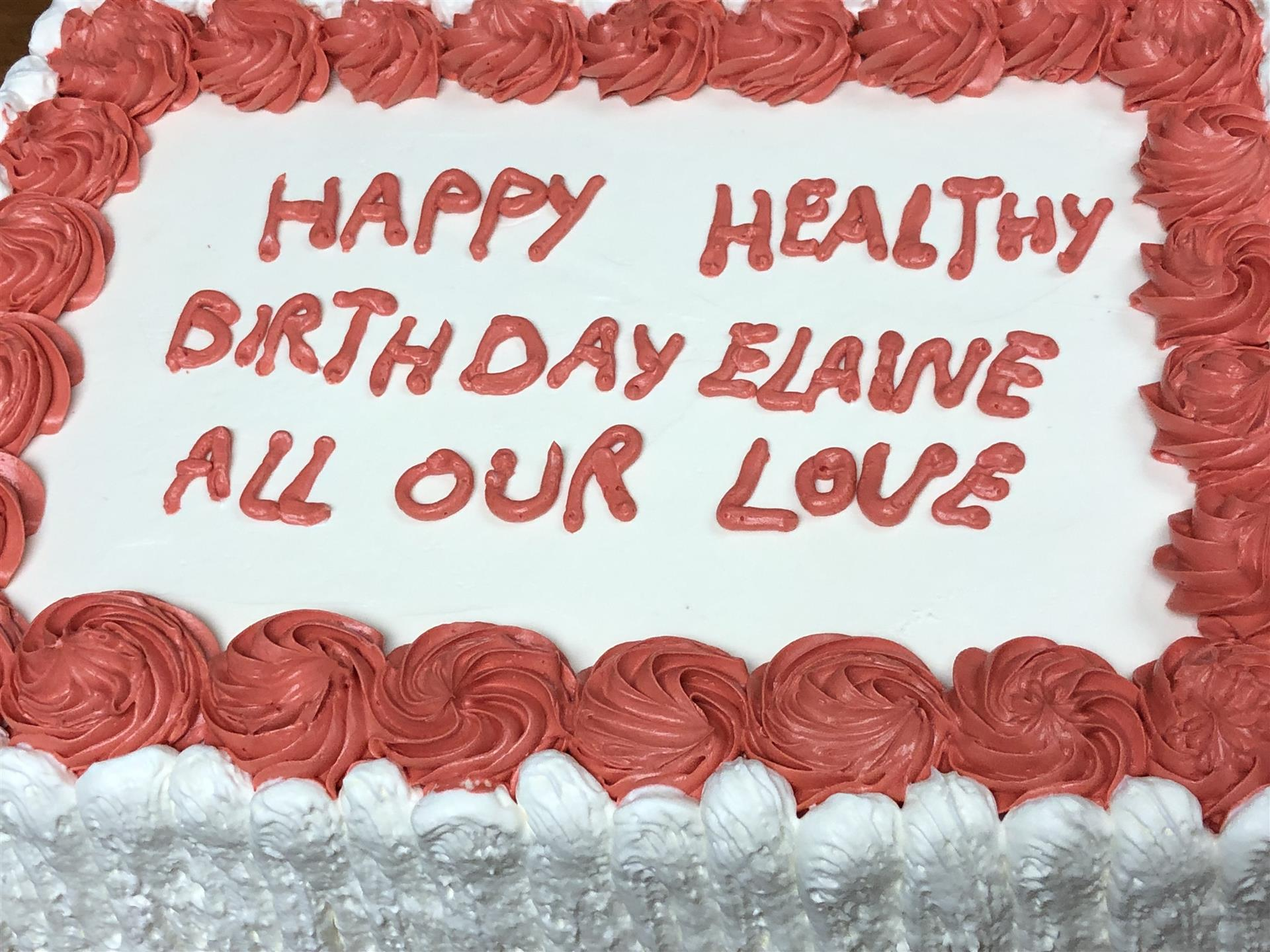 A cake that says Happy Healthy Birthday Elaine All Our Love, written in frosting