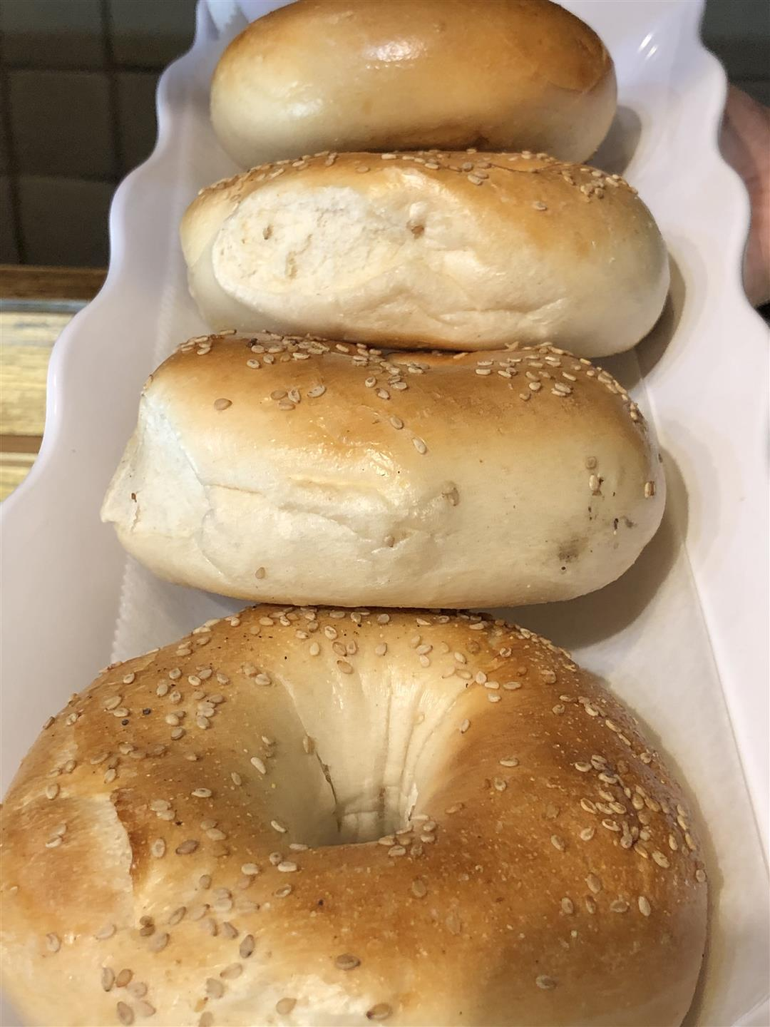four sesame bagels on a plate