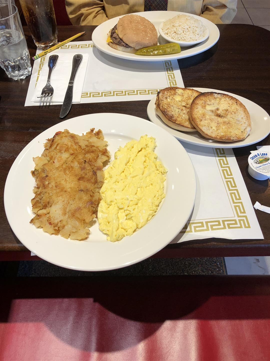 hash browns, scrambled eggs and a toasted bagel on a plate placed on the table