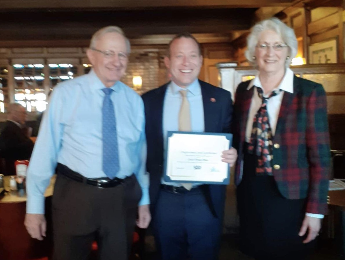 The owner taking a picture next to Congressman Josh Gottheimer while holding a certificate of recognition