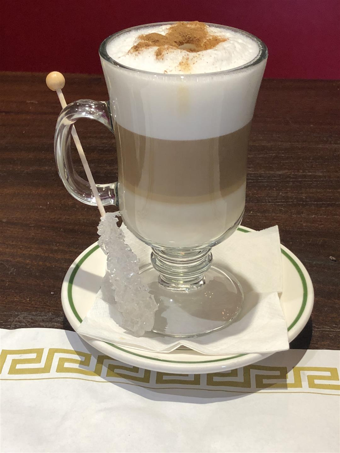 cappuccino with a sugar stick on the side