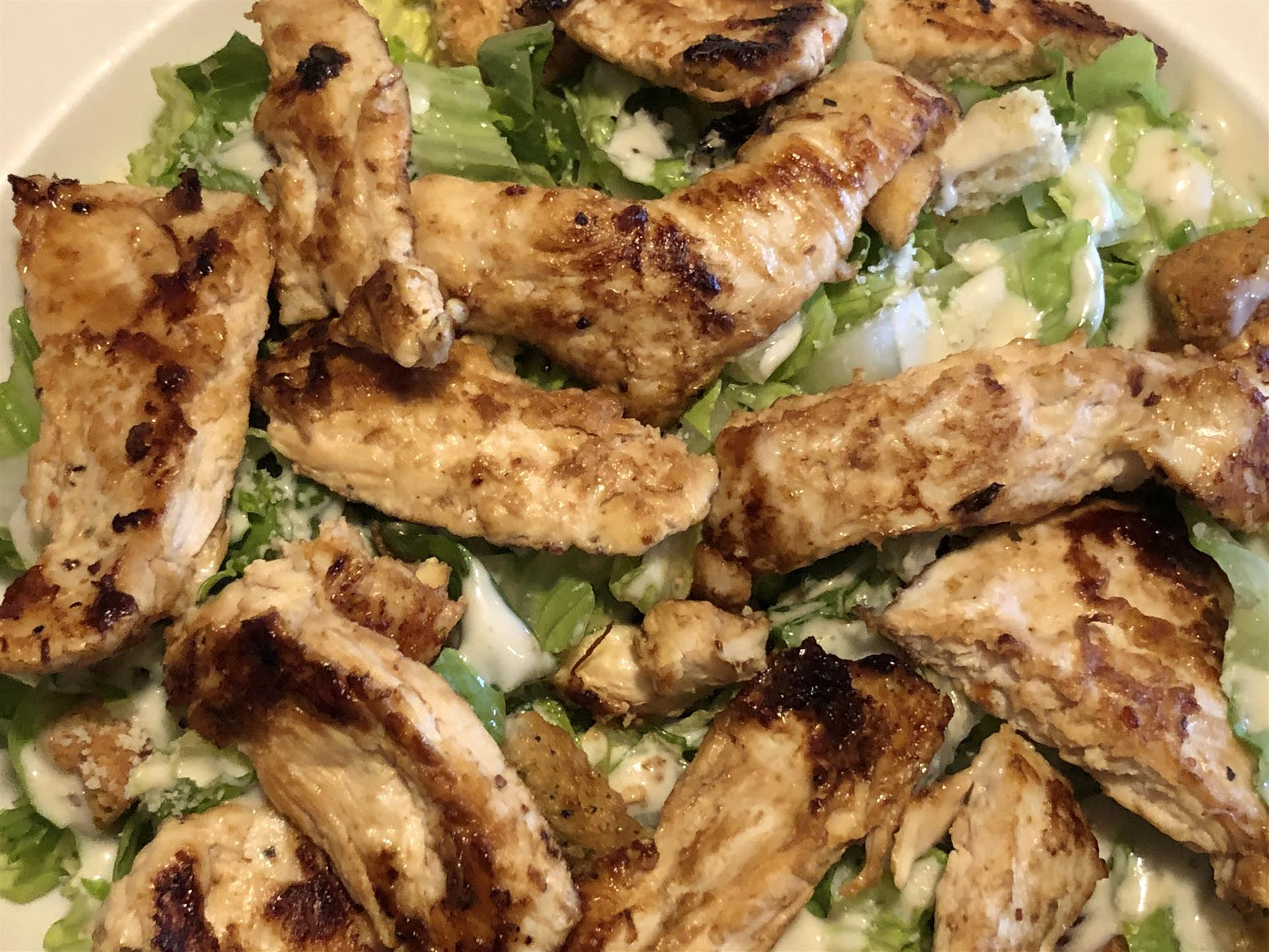 A close up of A grilled chicken cesar salad