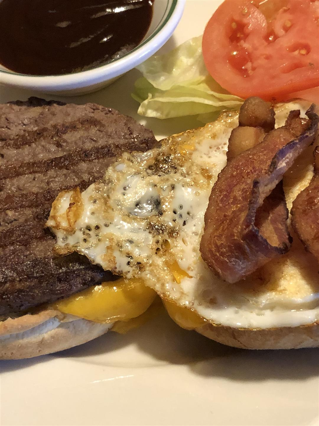 Texas Burger on a plate with bacon and an egg
