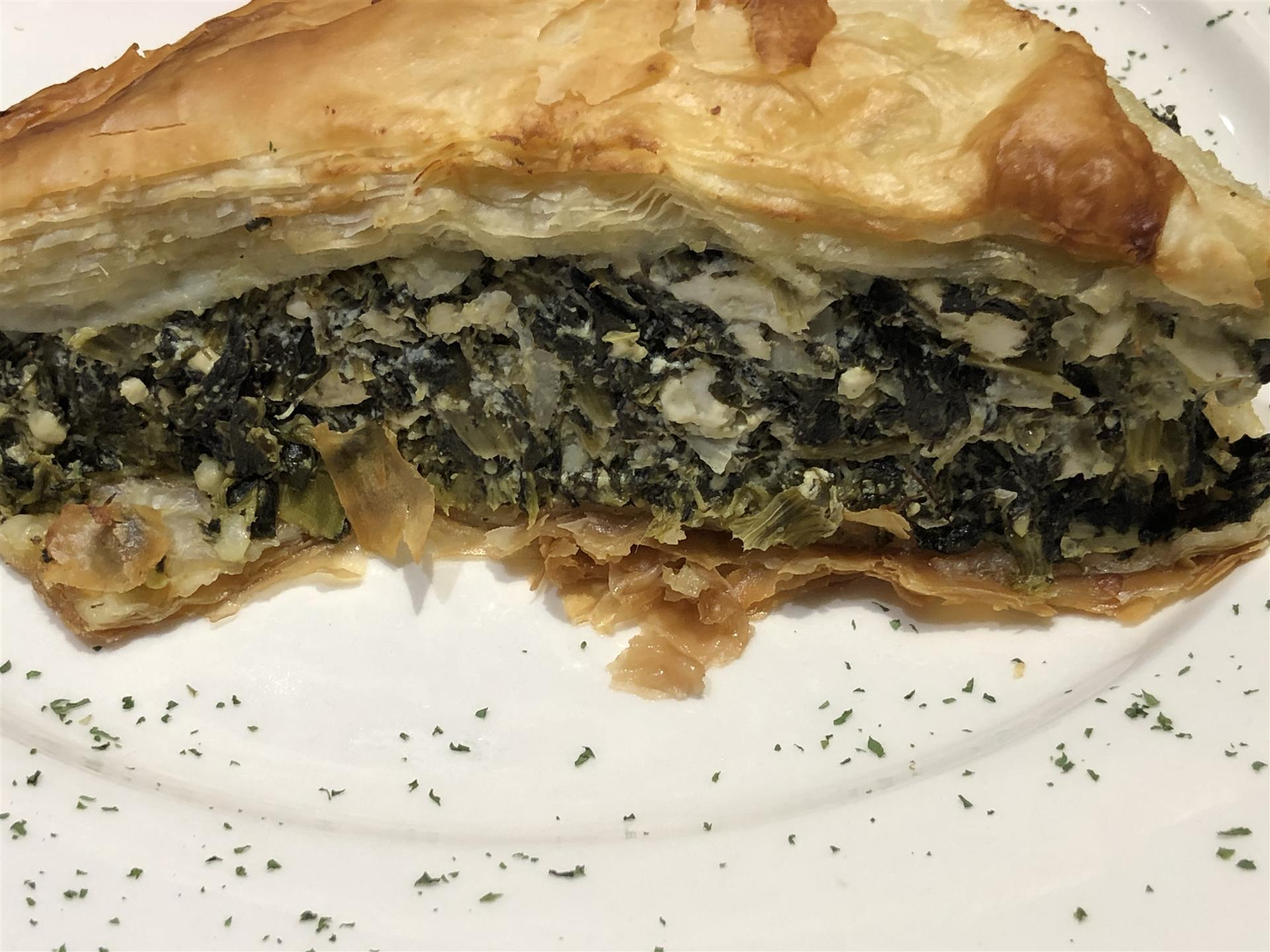a piece of spinach pie with a flaky crust
