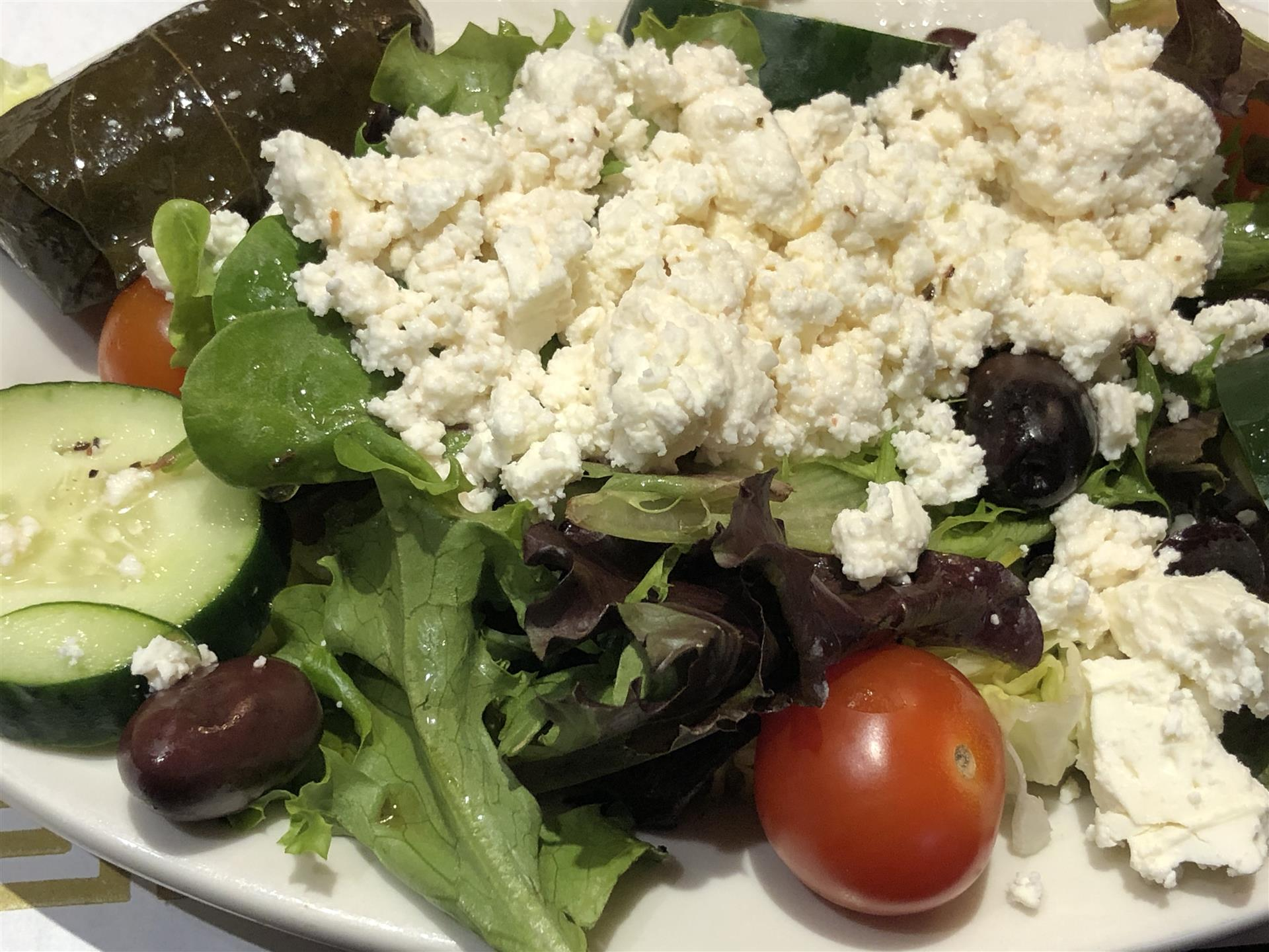 a Greek salad with olives, cucumbers, cherry tomatoes and feta cheese