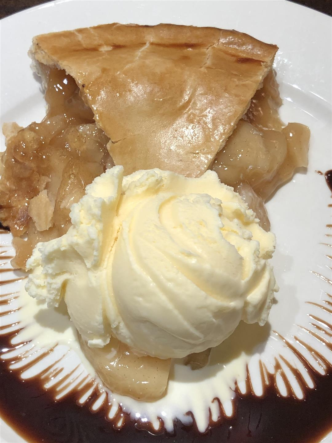 a slice of apple pie, with a scoop of vanilla ice cream beside it