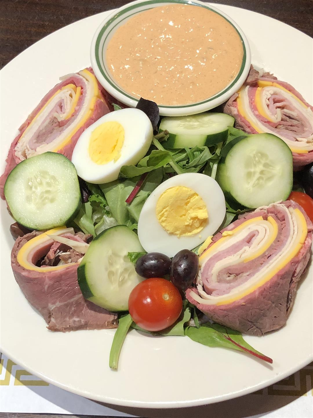 a chef's salad, with cucumbers, cherry tomatoes, and a hard boiled egg, with thousand island dressing on the side. Surrounding it is a ham, cheese and turkey roll that has been split into 4 pieces