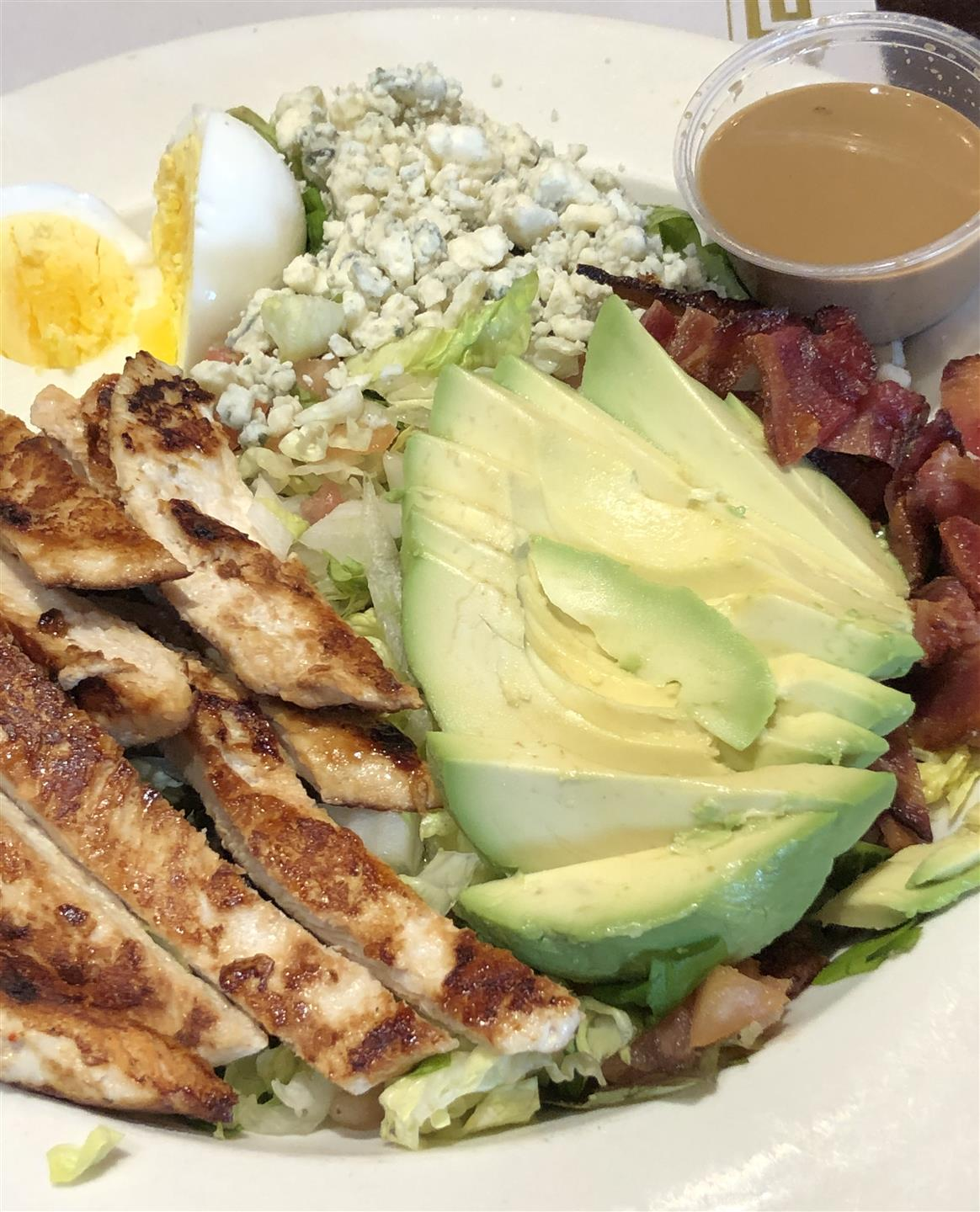 cobb salad: Chopped salad greens, tomato, crispy bacon, grilled chicken breast, hard-boiled egg, avocado, bleu cheese, with vinaigrette dressing.