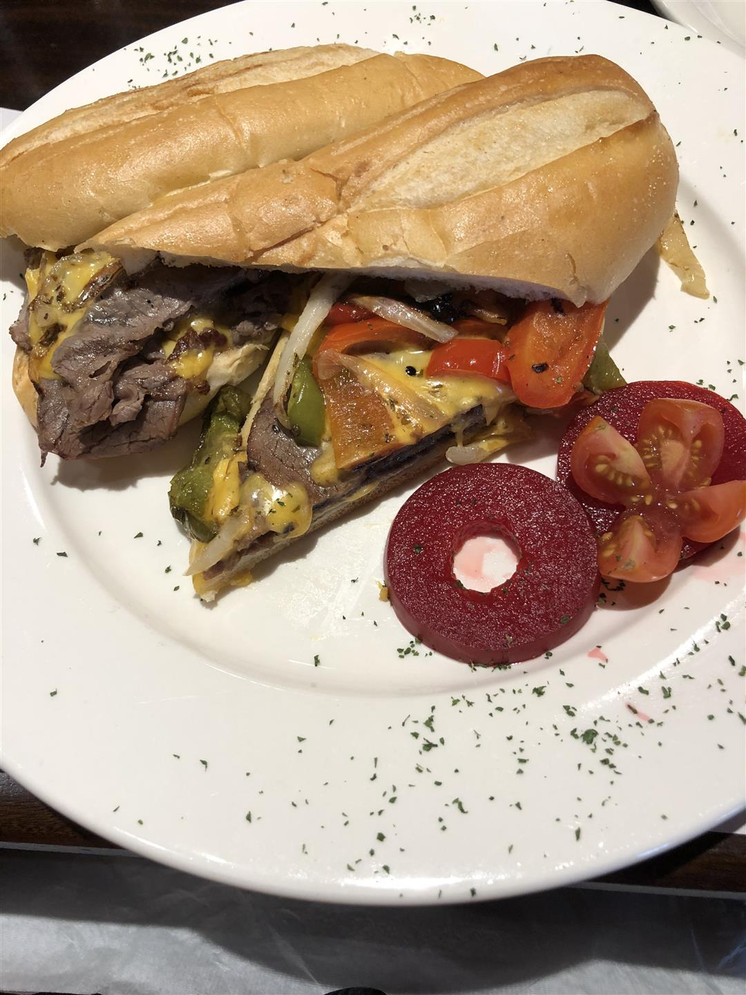 Philadelphia Cheese Steak on a plate cut in half with cranberry slices on the side