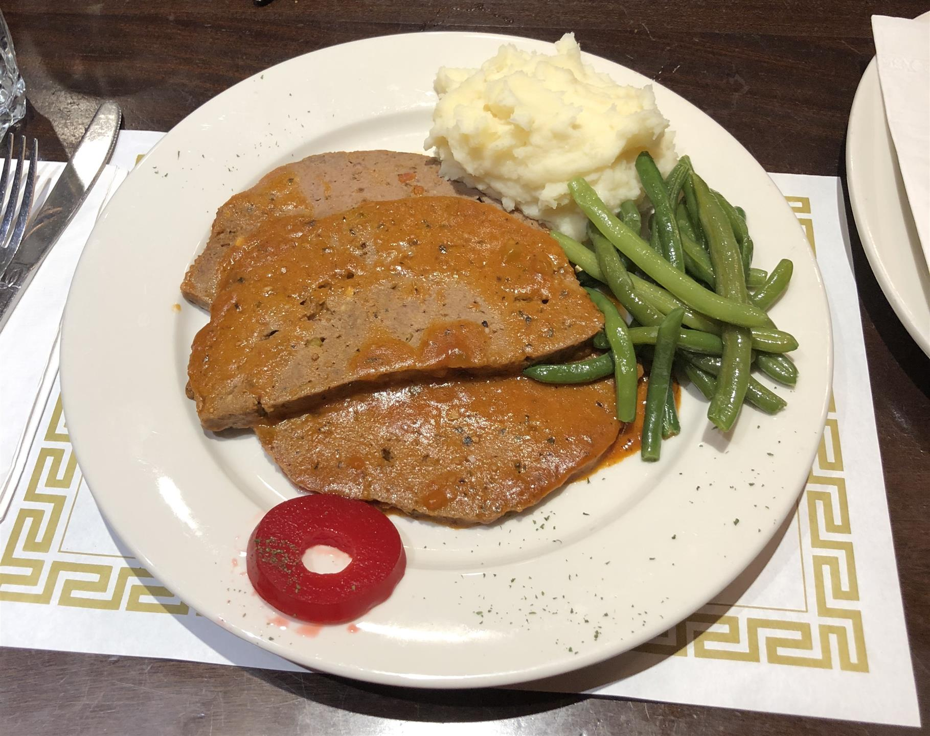 meatloaf on a plate with string beans and mashed potatoes