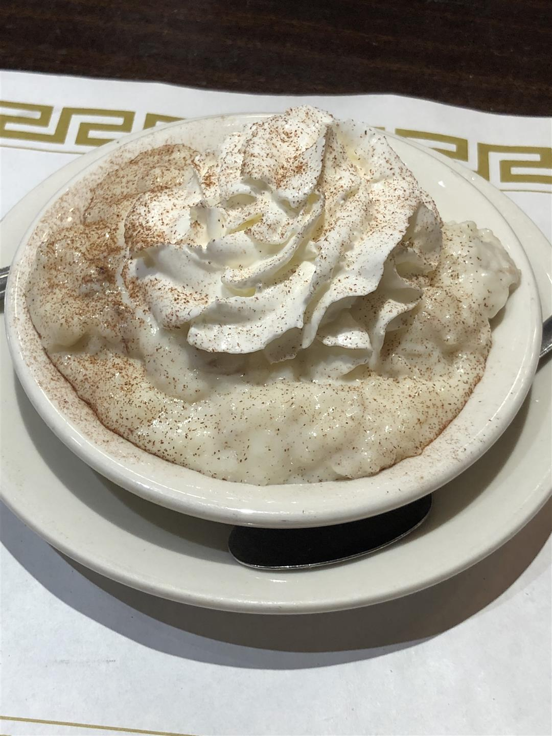 rice pudding in a bowl with whipped cream and cinnamon on top