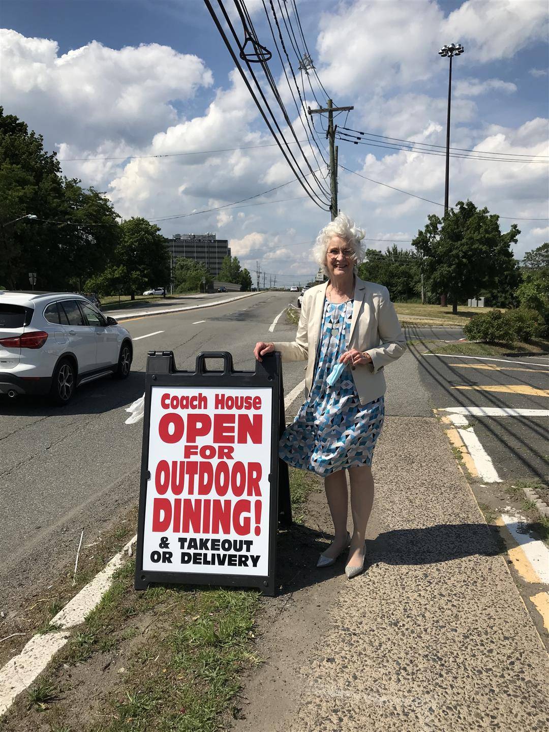 "Diner Owner holding a ""Now Open for Outdoor Dining"" sign"