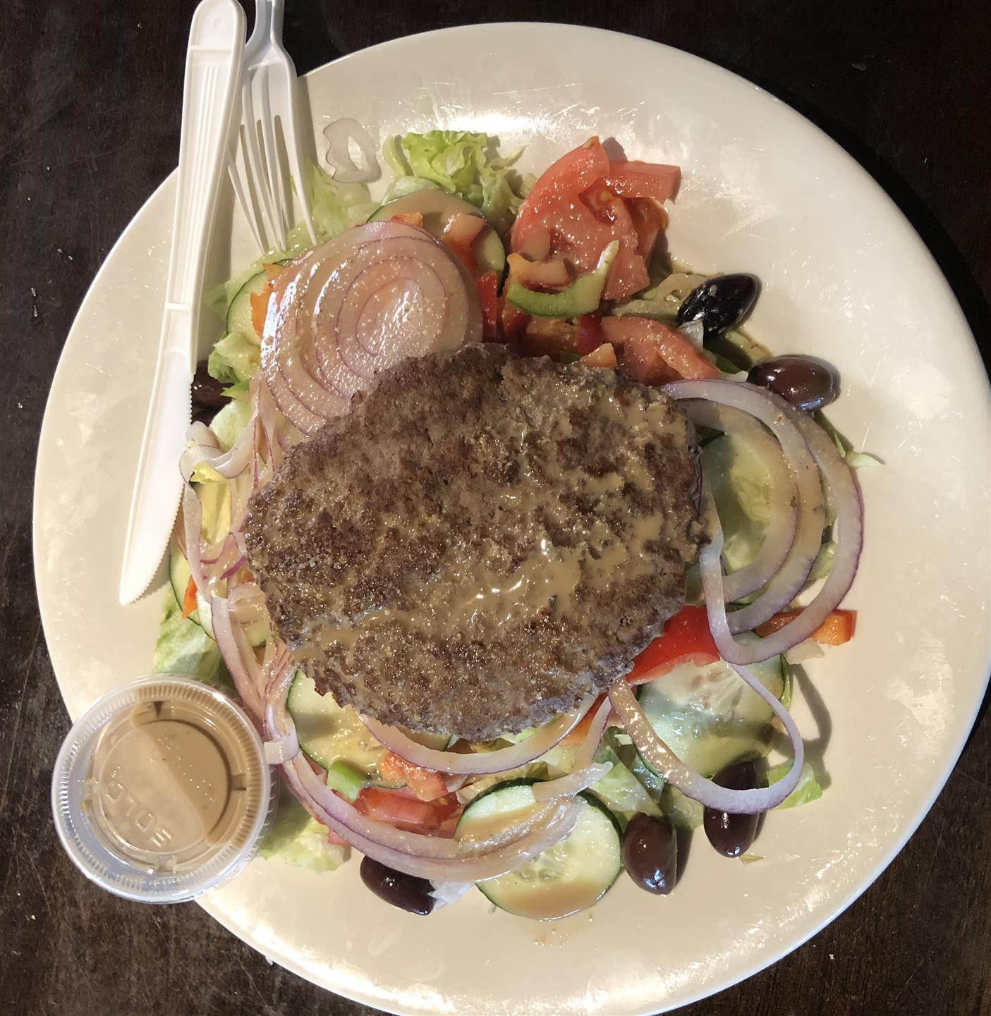 A delicious grilled hamburger on top of our scrumptious house salad