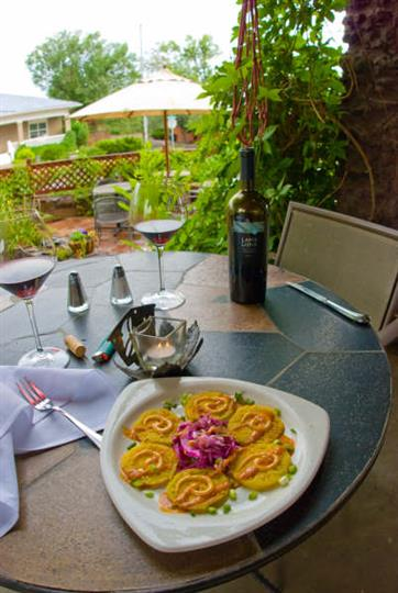 Colorful appetizer served with two glasses of wine on a patio table overlooking the garden