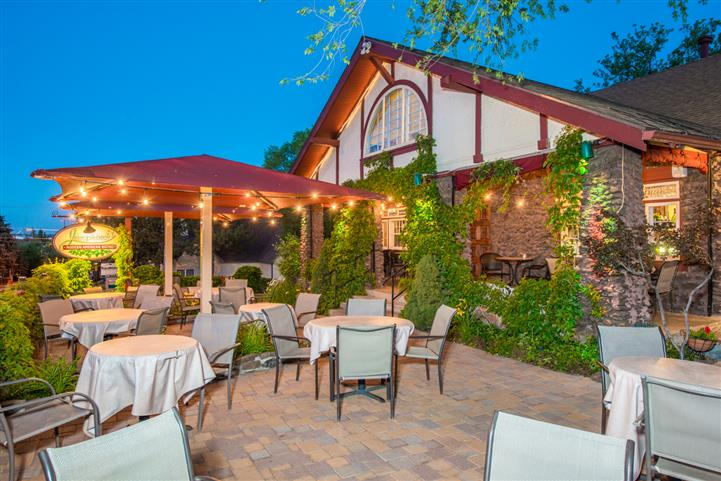 Exterior photo of the patio with the tables set for service and string lights in the background decorating the garden