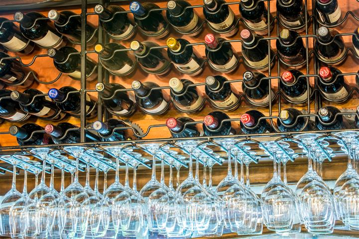 Wine bottles and wine glasses on display in a rail