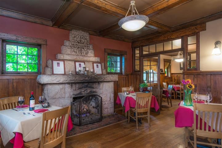 Interior shot of the dining hall with a big stone fireplace and tables set all around